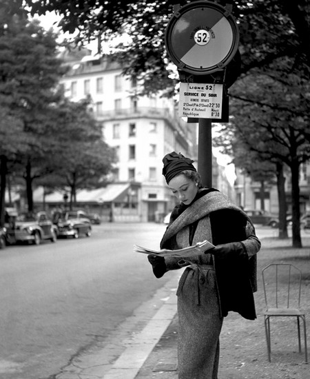 Sophie Litvak reading at bus stop in Paris wearing a Lanvin Castillo creation. Elle, September 1952.