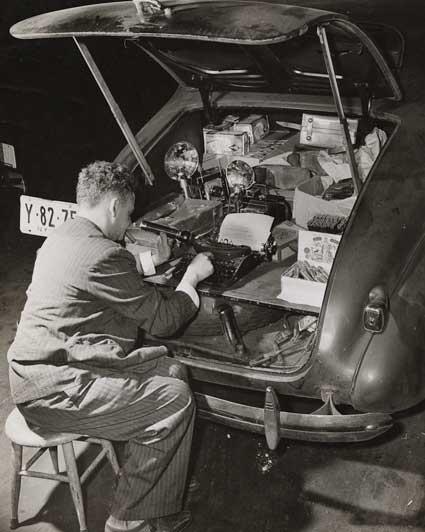Le photojournaliste Weegee et sa machine à écrire dans le coffre de sa Chevrolet en 1943